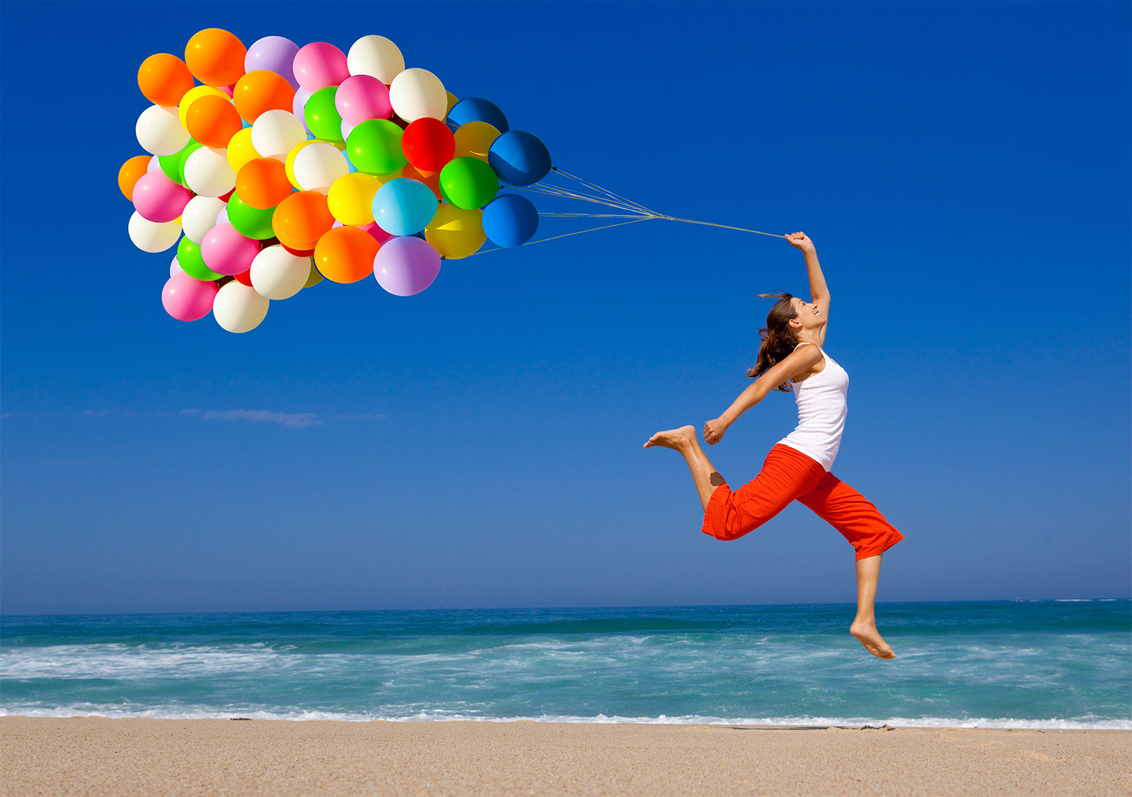 Lady with balloons on beach